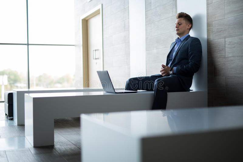 Business man sitting alone on a bench with laptop. Business man sitting alone on a bench with a laptop inside a building with a modern interior and large windows stock image
