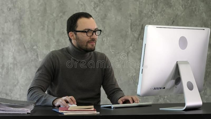 Business man sitting at desk in office and woking on the computer. royalty free stock photos