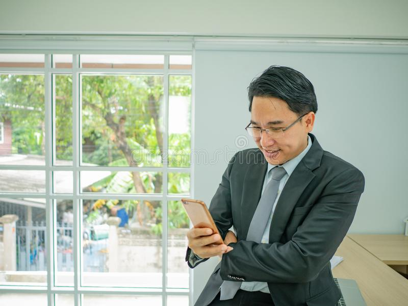 Business man sitting on his disk and check his mobile phone stock images