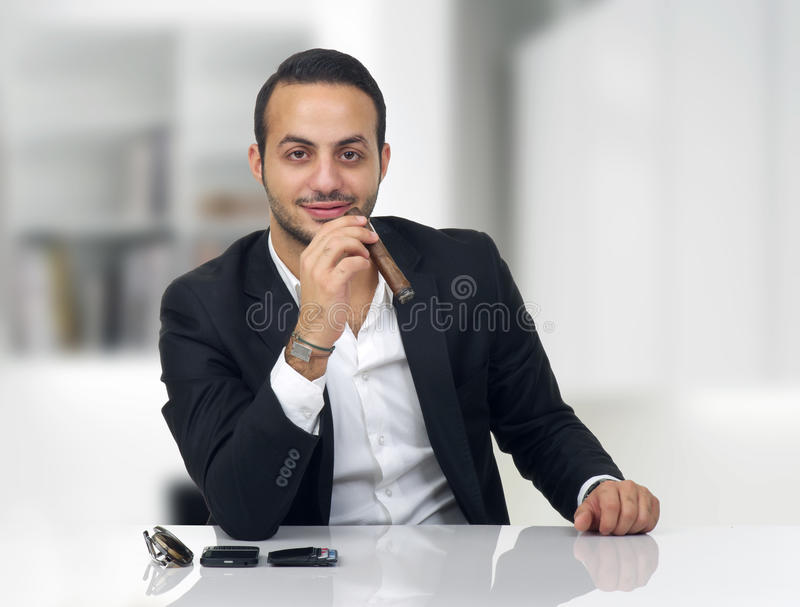 Business Man Sitting In His Office And Smoking Cigar Stock