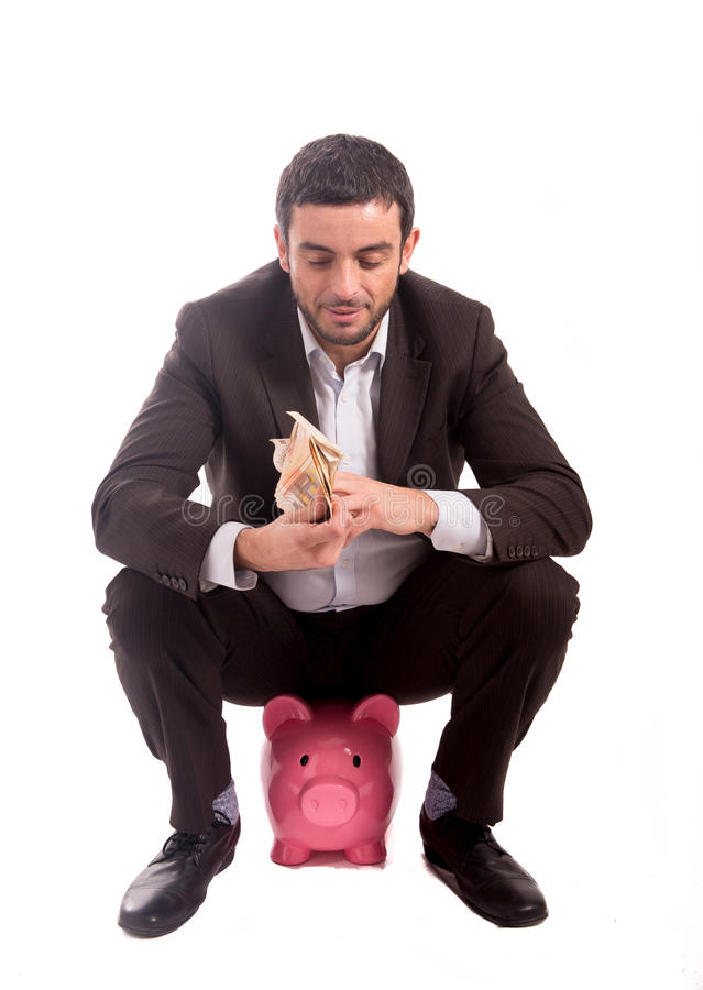 Business man sitting on piggy bank counting money euros stock image