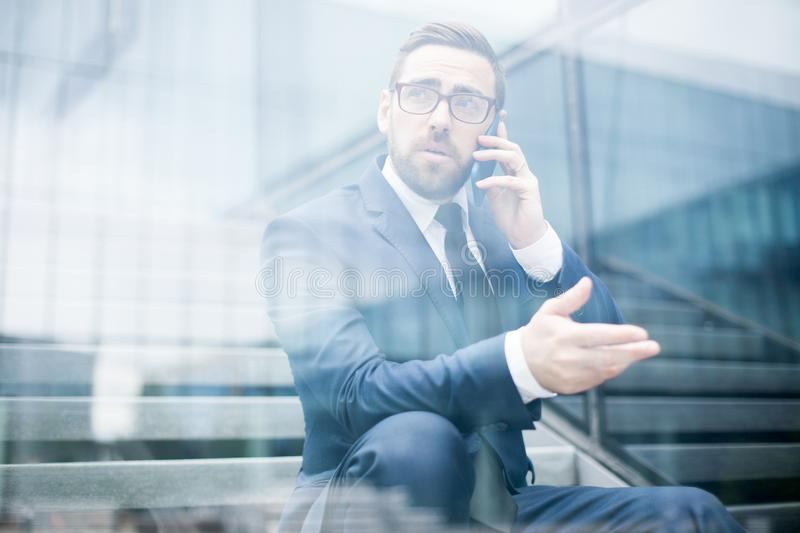 Business man sitting on steps talking smartphone. Young stylish male in business dress, eyeglasses talking mobile phone, extending hand and looking away behind royalty free stock images