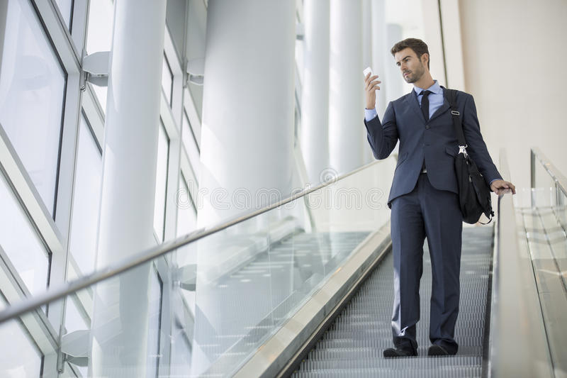 Business man sitting talking on cell phone while on escalator stock photo
