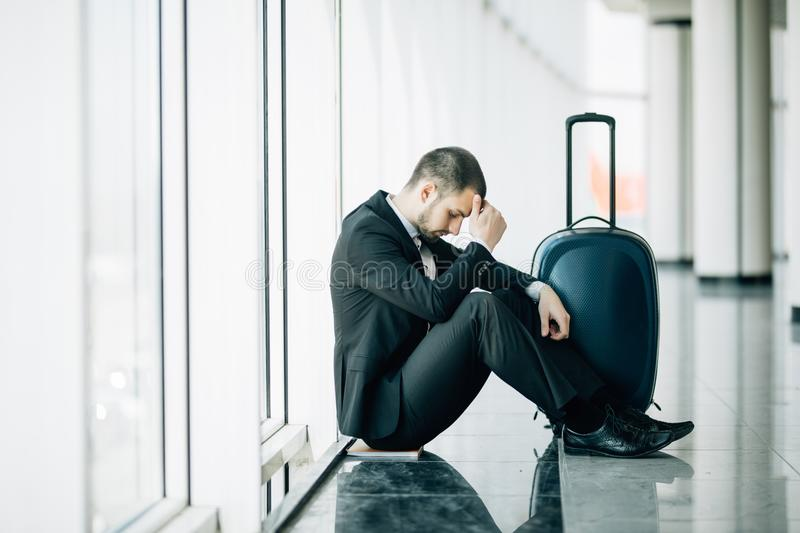 Business man sitting at the terminal airport on the floor with suitcase flight delay, two hands touch at head, headache, waiting t stock photography