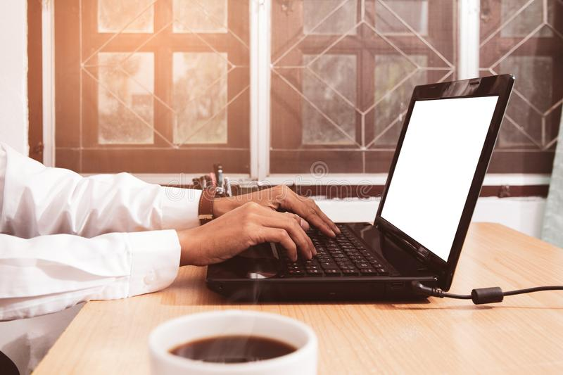 Business man sitting using laptop with blank screen on desk in office at home royalty free stock images