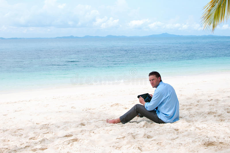 Business man sitting and working on the beach