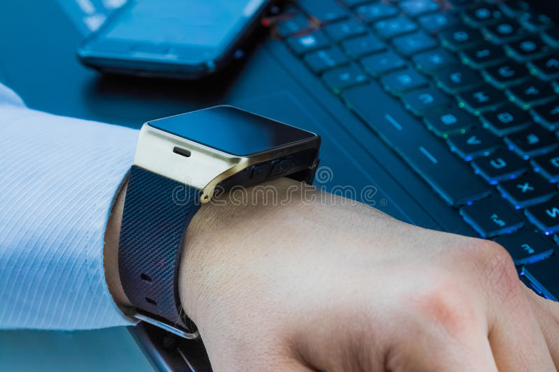 Business man with smartwatch app near computer pc keyboard and smartphone on daily light. New technology concept stock photos
