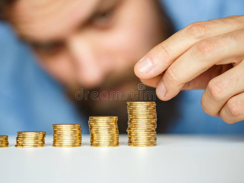Business man stacking gold coins into increasing columns. Savings, beard business man stacking gold coins into increasing columns royalty free stock image