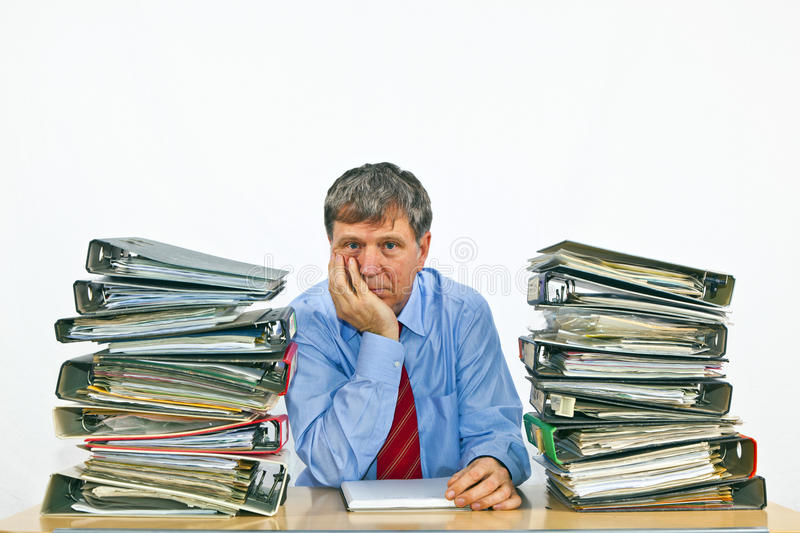 Business man with stacks of ring binders on his desk royalty free stock image