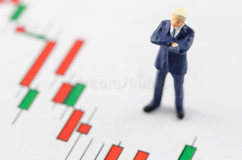 Business man standing on the candlestick stock chart. Miniature business man standing on the candlestick stock chart royalty free stock images