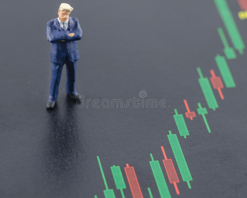 Business man standing on the candlestick stock chart. Miniature business man standing on the candlestick stock chart royalty free stock photo