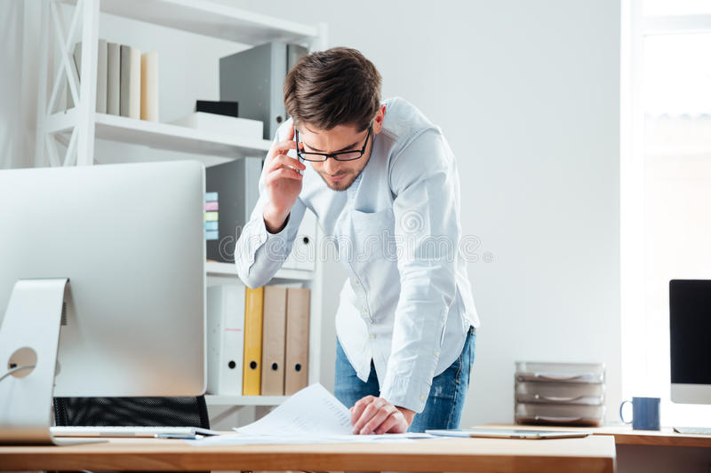 Business man standing at desk working on documents with mobilephone. Young handsoome business man standing at desk working on documents with mobile phoone in stock photos