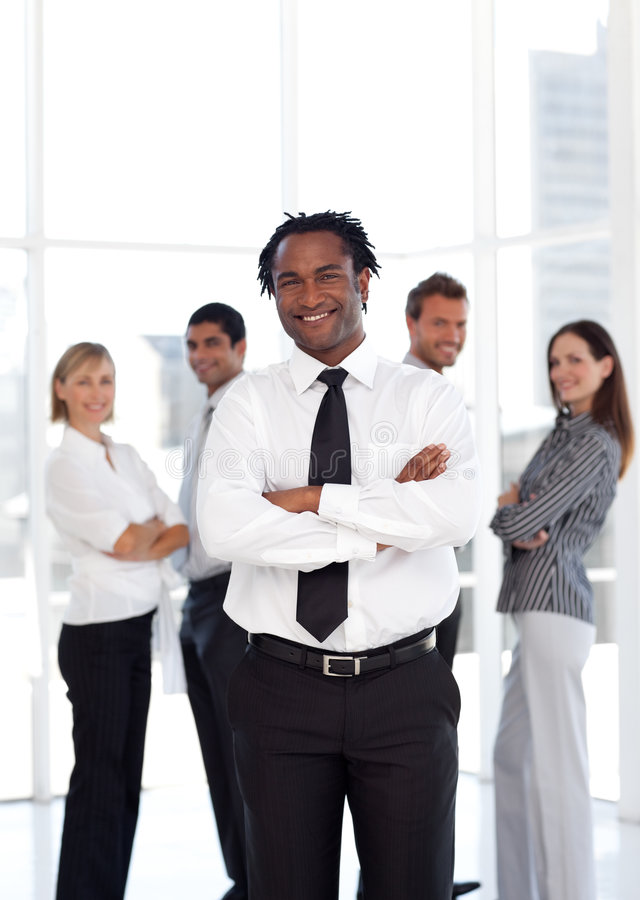 Business man standing in front of co-workers stock photos
