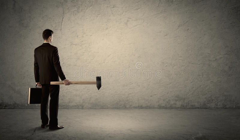 Business man standing in front of a grungy wall with a hammer. Business man standing in front of a grungy copyspace wall with a hammer royalty free stock photos
