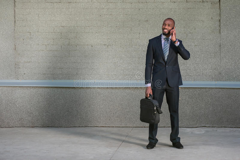 Business man standing with his briefcase, and he uses the phone stock photo