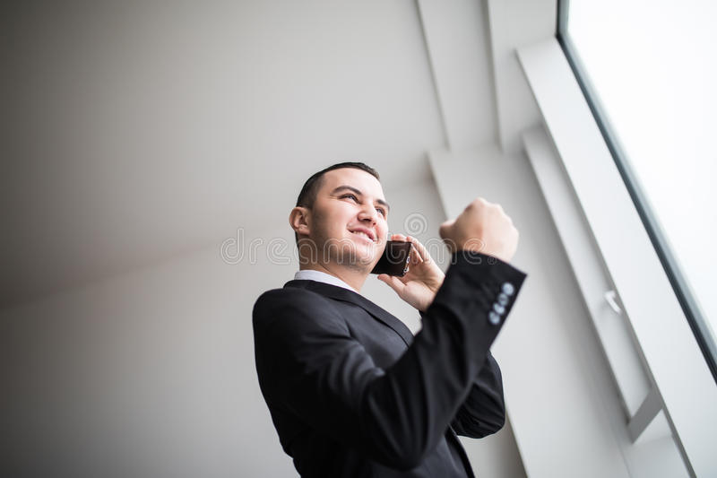 Business man standing next to large windows of his top floor office, looking at the view of the city while take good news from his royalty free stock image
