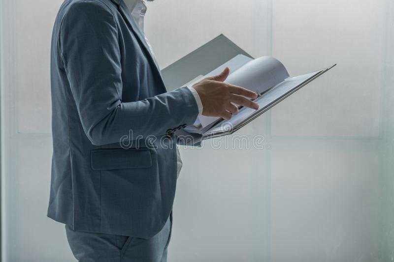 Business man standing and reviewing a document in file. stock photos