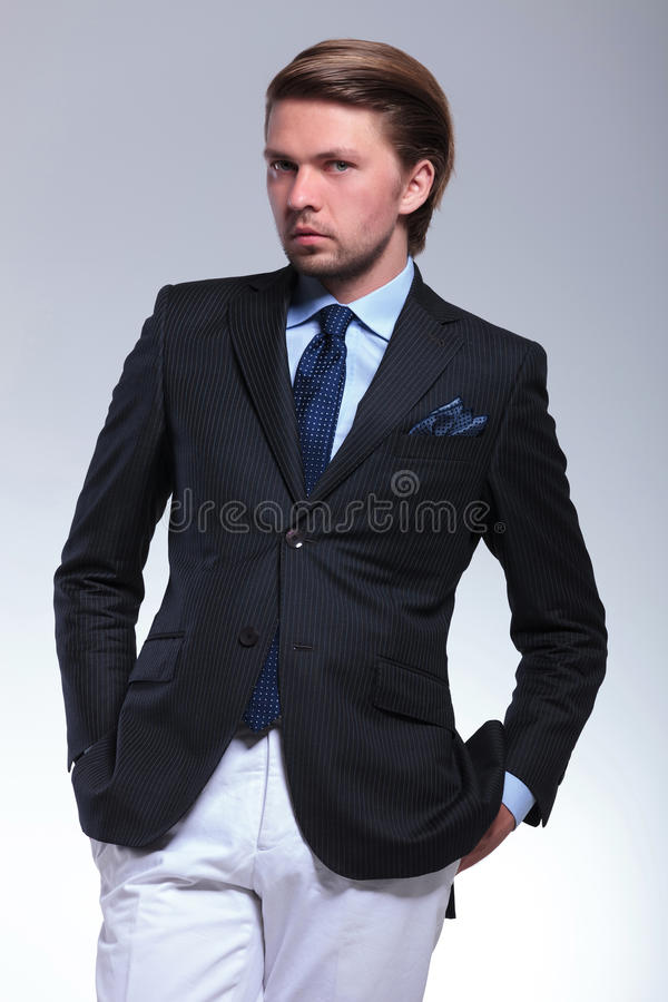 Business man stands with hands in pockets royalty free stock photo