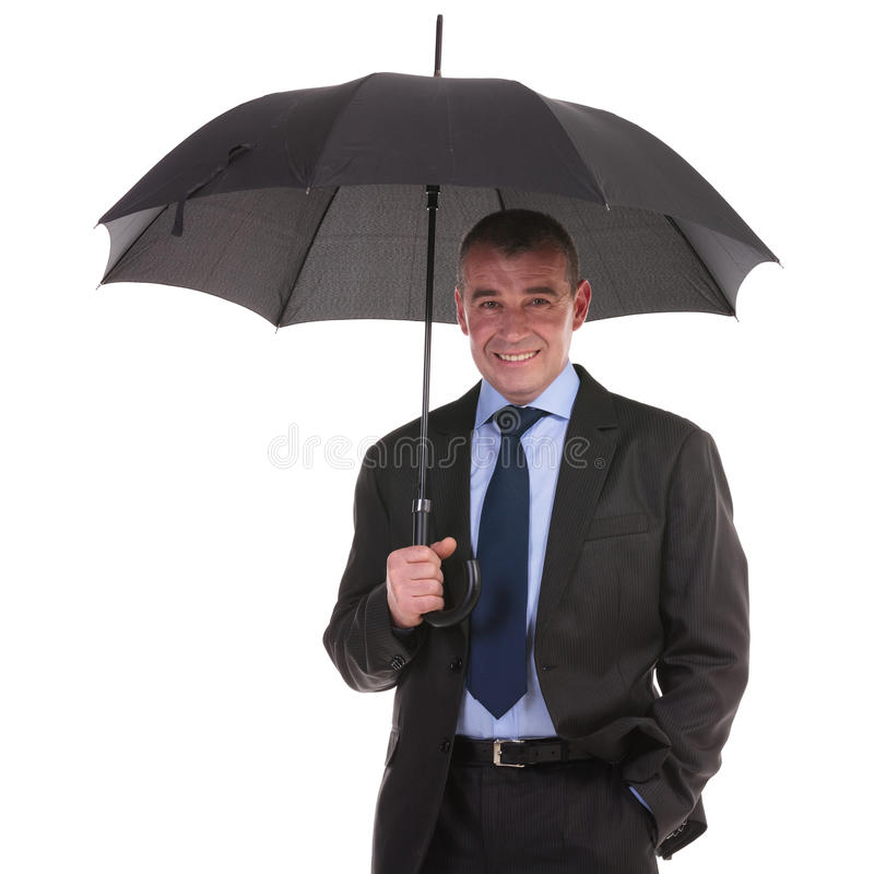 Business man stands under umbrella royalty free stock photography