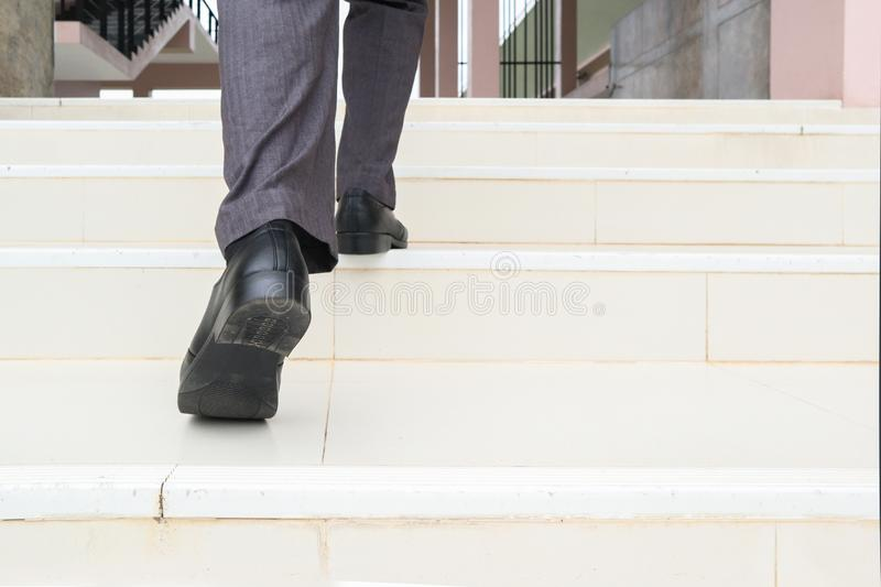 Business man step up stair.Lower part of Man in business shoes walking up stair,People lifestyle successful and competition royalty free stock photo