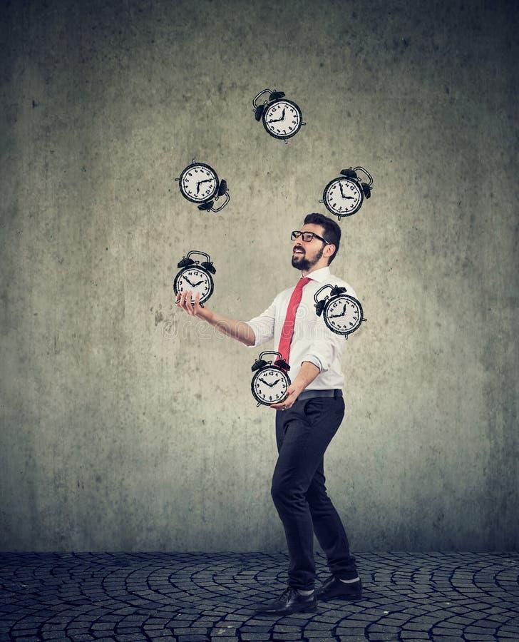 Business man successfully juggling managing his time. Happy young business man successfully juggling alarm clocks managing his stock photography