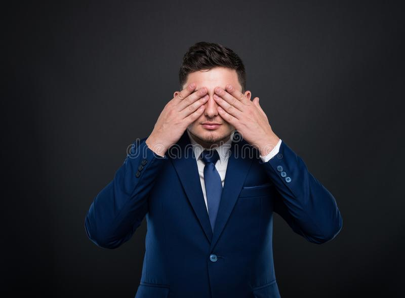 Business man in suit closes his eyes royalty free stock image