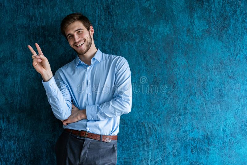 Business man in a suit giving the victory sign on blue background. stock photos