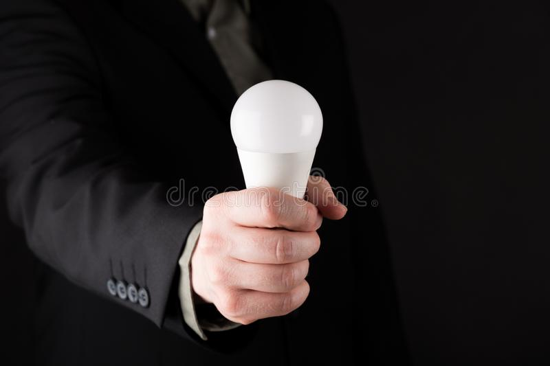 Business man in suit Holding a white light bulb in hand, isolated on gradient black background stock photo
