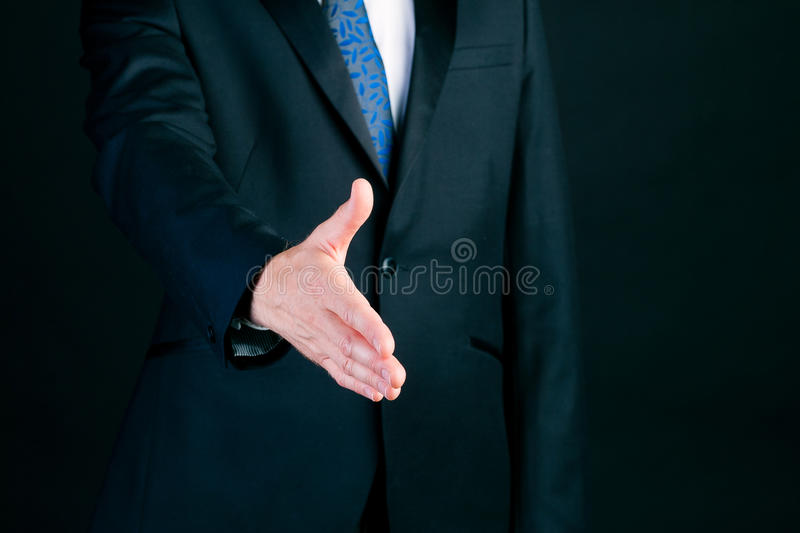 Business man in suit offering handshake. Business man or manager in suit offering handshake in front of black background royalty free stock photography