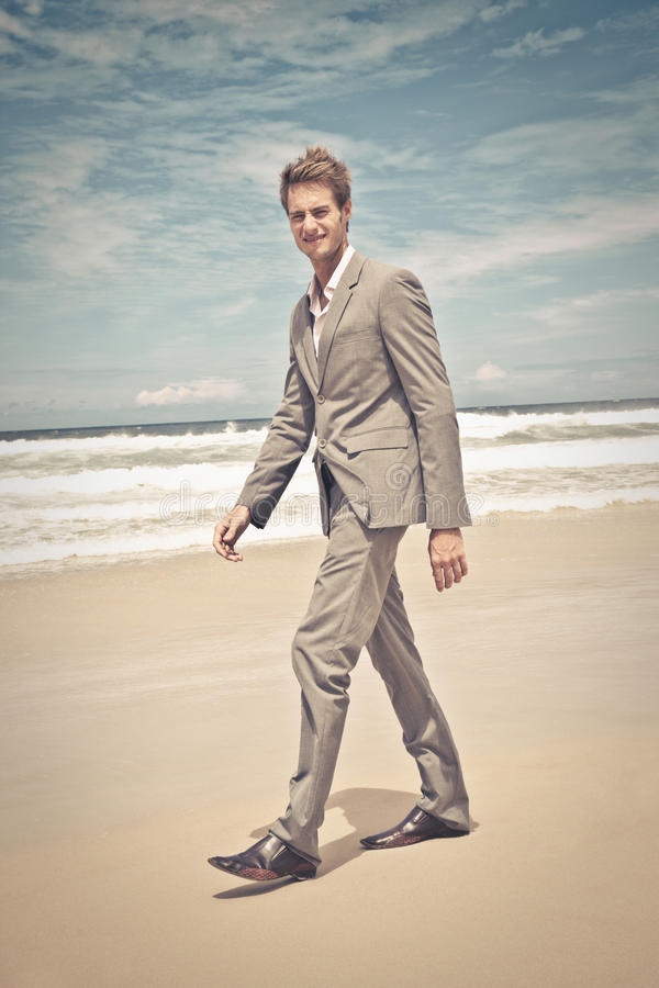 Business man in suit walking on the beach royalty free stock photography