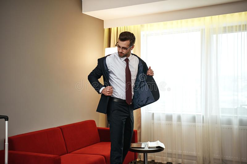 Business man with suitcase takes off his jacket near sofa at hotel room stock photos