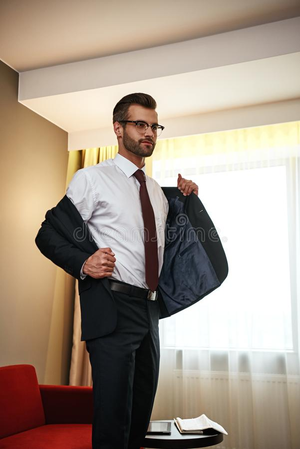 Business man takes off his jacket near sofa at hotel room stock photography