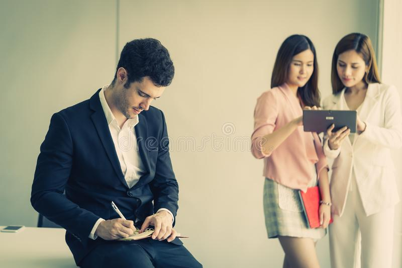 Business man taking note in front of two female office worker royalty free stock photos