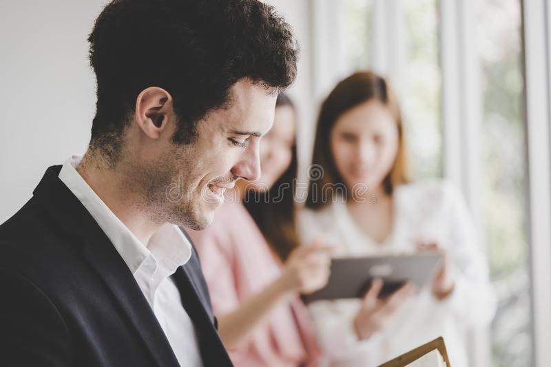 Business man taking note in front of two female office worker stock image