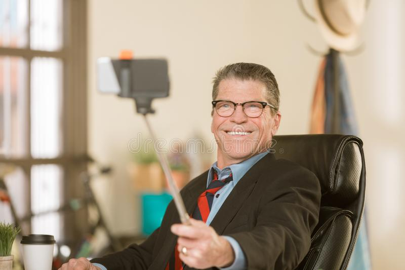 Business Man Taking a Silly Selife. Business man taking a silly selfie with a selfie-stick i his office royalty free stock photos