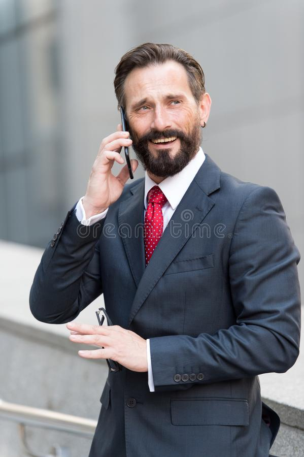 Business man talking active with the client on a cell phone out of office building. Handsome bearded manager outdoor makes call stock image