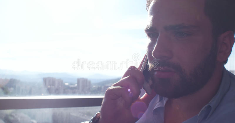 Business Man Talking On Cell Phone At Home. With sun flares coming from window stock image