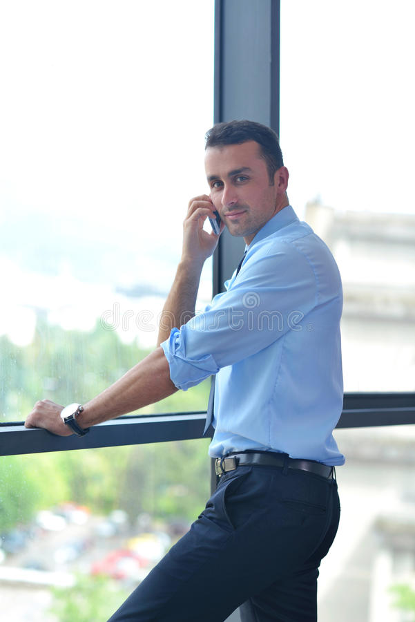 Business man talking by cellphone. In office stock photos