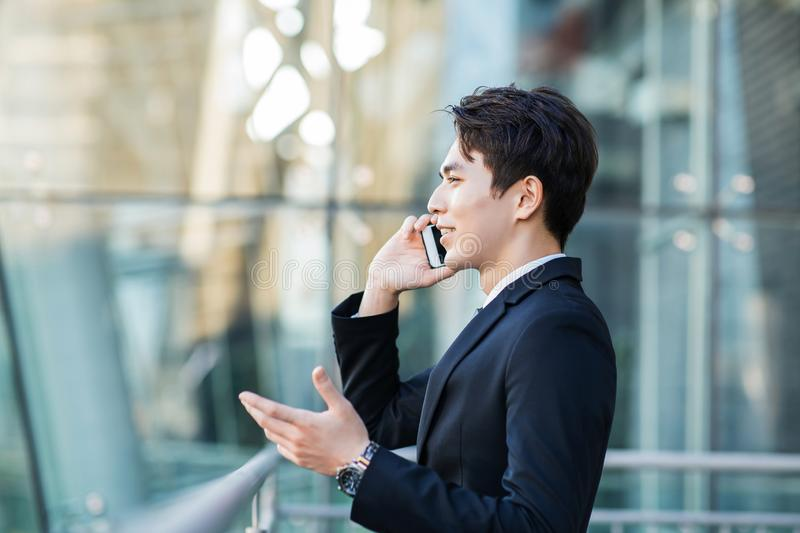 Business man talking on the phone with city building background stock photos
