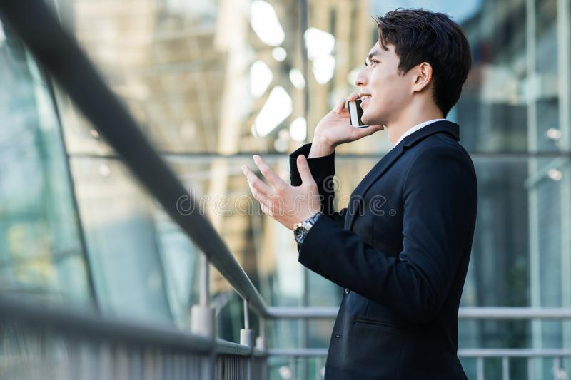 Business man talking on the phone with city building background royalty free stock photo