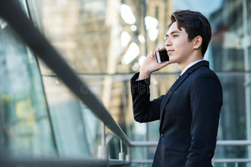 Business man talking on the phone with city building background stock images