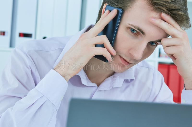 Close-up portrait of white collar talking to customer on mobile phone in office at workplace by laptop. stock photo