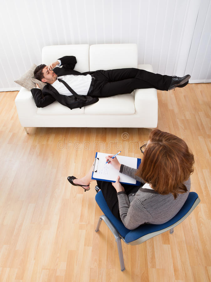 Business man talking to his psychiatrist explaining something. Business men reclining comfortably on a couch talking to his psychiatrist explaining something stock images