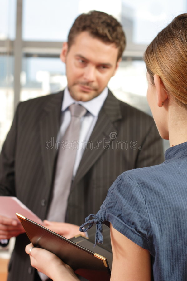 Business man talking to his secretary in the office stock photo
