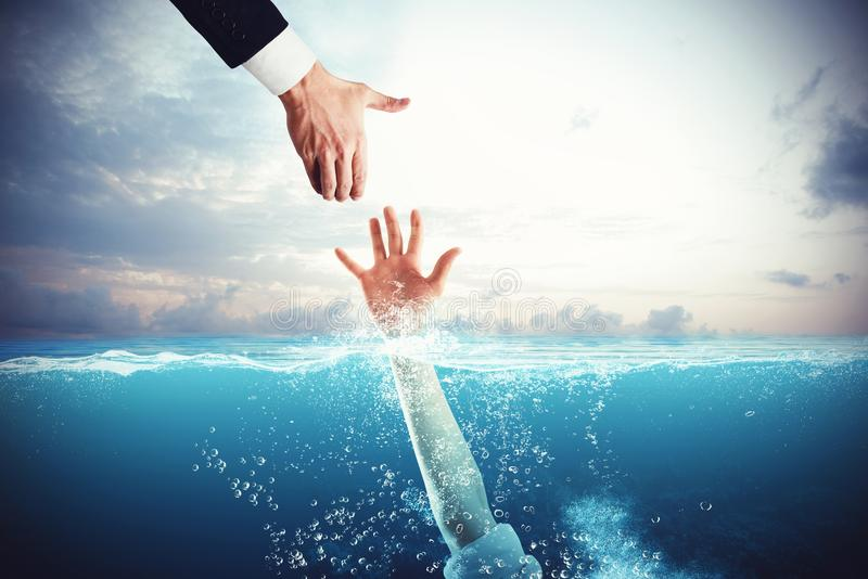 Help in the difficulty. Business man tends his hand to save a person drowning stock images