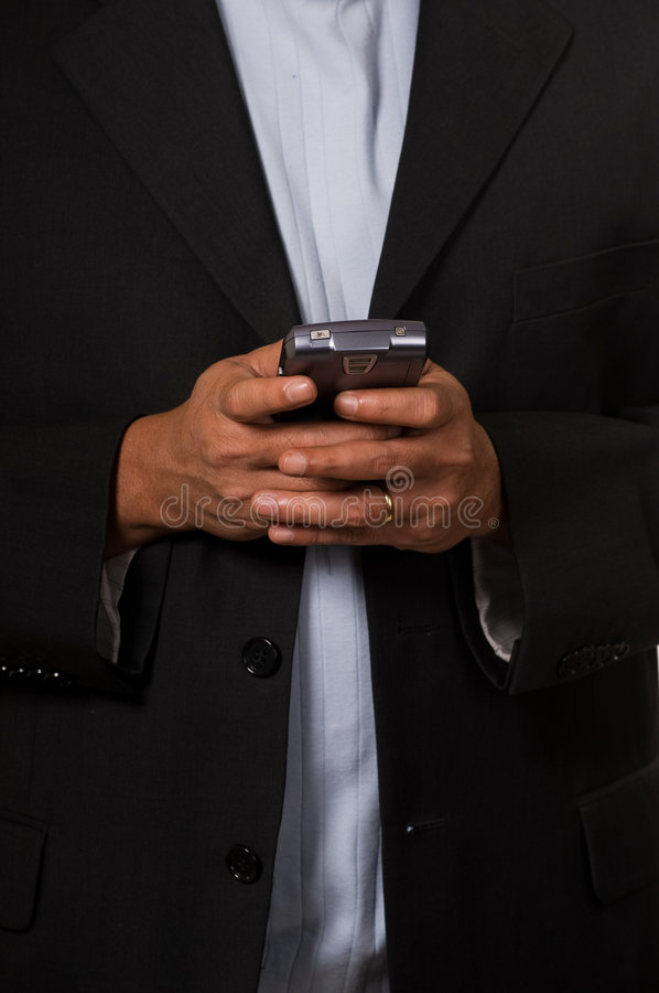 Business man texting. Close up of a man's hands holding and text messager royalty free stock photography