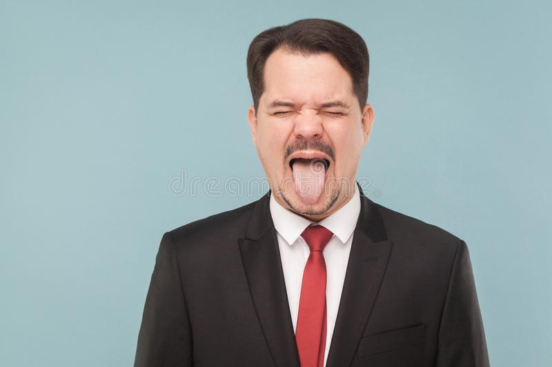 Business man tongue out, closed eyes. Closeup portrait of crazy man in classic suit, tongue out, and roar. indoor studio shot. isolated on light blue background royalty free stock photography