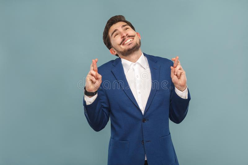 Business man toothy smiling, crossed fingers wish, pray and hope stock photos