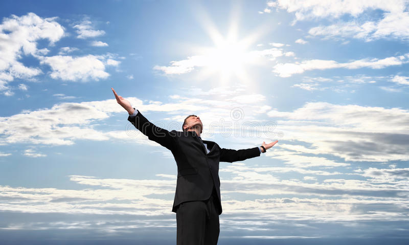 Business man on top of success, open arms to the sky royalty free stock images