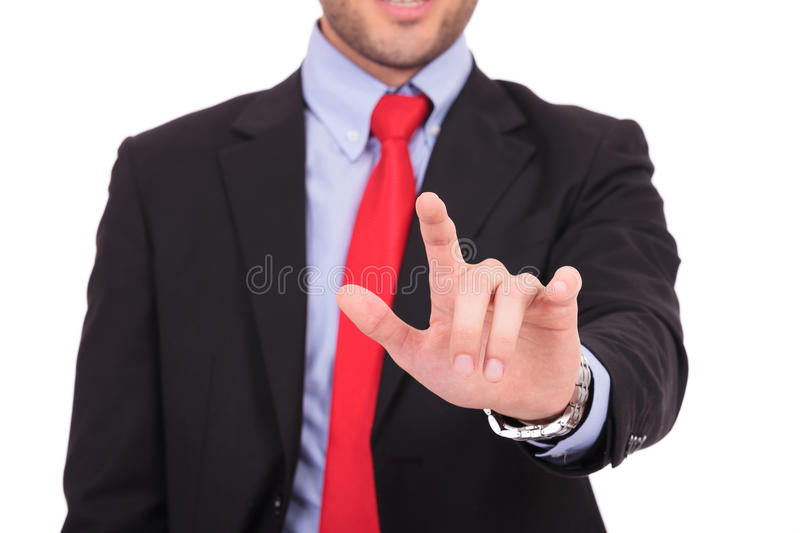 Business man touches imaginary screen. Portrait of young business man touching an imaginary screen against white background stock images